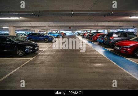 Underground multi storey car park / parking garage with cars parked on both sides.