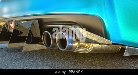 Blue car with dual exhaust pipe and tail spikes - Stock Photo