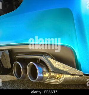 Metallic blue car with dual exhaust pipe - Stock Photo