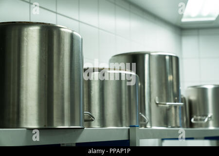 row of large metal cooking pots in an industrial size restaurant kithcen on a metal shelf - Stock Photo
