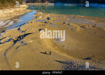 Deflated storage lake with tourists in winter, Sylvenstein Lake, Isartal, Lenggries, Upper Bavaria, Bavaria, Germany, Europe - Stock Photo