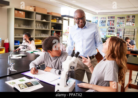 High School Students With Tutor Using Microscope In Biology Class - Stock Photo