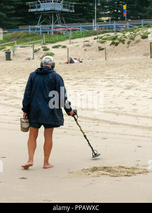 Man with METAL DETECTOR t a beach outside Sydney Australia,search for hidden metal objects - Stock Photo