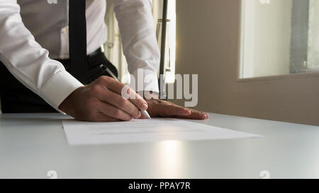 Businessman in office signing contract, document or legal papers with a natural sunlight from behind. - Stock Photo