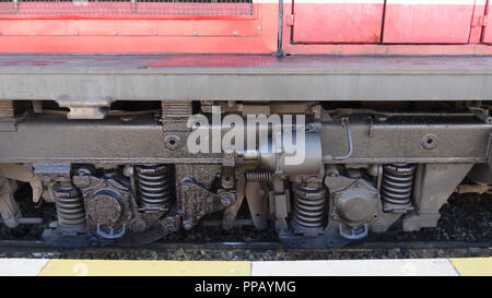 Red train, Diesel locomotive, Close up detail of Suspension, shock absorber and wheels freight wagon - Diesel railcar - Stock Photo