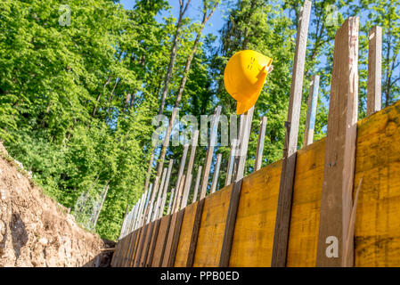 Bright Yellow Hard Hat Hanging on Post of Unfinished Building Foundation Under Construction in Wooded Forest Area. - Stock Photo