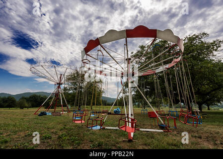 Old abandoned Carousel with Chairs. Merry-go-round in the Countryside - Stock Photo