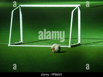 Soccer ball and goalpost on stadium field at night - Stock Photo