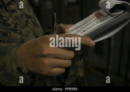 Cpl. Rosetta B. Poveromo, an automotive maintenance technician with the 31st Marine Expeditionary Unit, verifies gear serial numbers aboard the amphibious assault ship USS Wasp (LHD 1) at White Beach Naval Facility, Okinawa, Japan, Aug. 21, 2018. Poveromo, a native of West Winfield, New York, graduated Mount Markham High School in June 2016 before enlisting in the Marine Corps in September of the same year. The 31st MEU, the Marine Corps' only continuously forward-deployed MEU, provides a flexible force ready to perform a wide-range of military operations in the Indo-Pacific region. - Stock Photo