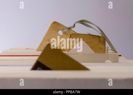 view along the top of line of paperbacks with different types of bookmarks (some improvised) in each of them - Stock Photo