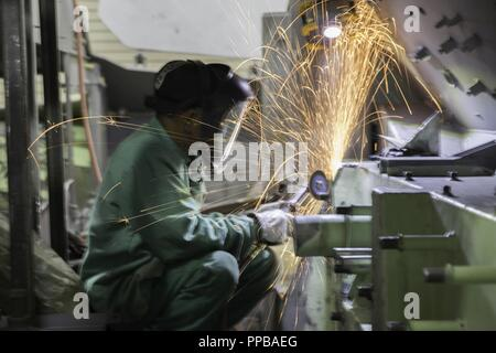 Department of Defense civilian employee Sithon Lag, welder, uses an angle grinder to debur metal on a Light Armored Vehicle during the rebuild process at the production plant aboard Marine Corps Logistics Base Barstow, California, Aug. 17. Sparks fly in this photo and show just how important safety gear is to the DoD civilian employees. - Stock Photo