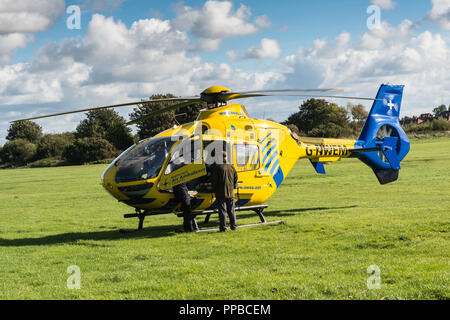 The North West air ambulance landed in a grassy field after responding to an emergency in Blackpool, Lancashire, UK. - Stock Photo