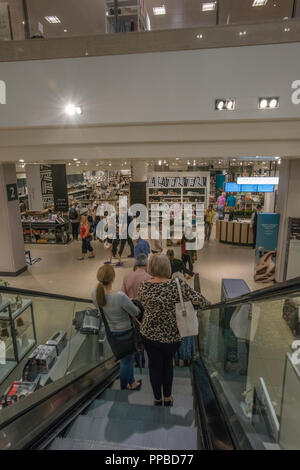 a group of ladies on an escalator in west quay shopping centre in Southampton. - Stock Photo