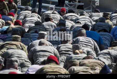 Attendees participate in memorial push-ups during Tech. Sgt. John Chapman's name unveiling ceremony at the Air Force Memorial, in Arlington, Va., Aug. 24, 2018. Chapman was posthumously awarded the Medal of Honor for actions on Takur Ghar mountain in Afghanistan on March 4, 2002. An elite special operations team was ambushed by the enemy and came under heavy fire from multiple directions. Chapman immediately charged an enemy bunker through high-deep snow and killed all enemy occupants. Courageously moving from cover to assault a second machine gun bunker, he was injured by enemy fire. Despite  - Stock Photo