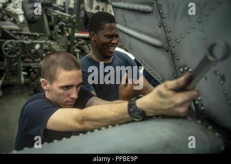 """CHINA SEA (Aug. 24, 2018) – Aviation Structural Mechanics 3rd Class Daryl Beres and Demario Murraychambers perform maintenance on an MH-60S Sea Hawk helicopter, attached to the """"Blackjacks"""" of Helicopter Sea Combat Squadron (HSC) 21, in the hangar bay of Wasp-class amphibious assault ship USS Essex (LHD 2) during a regularly scheduled deployment of the Essex Amphibious Ready Group (ARG) and 13th Marine Expeditionary Unit (MEU). The Essex ARG/13th MEU is a capable and lethal Navy-Marine Corps team deployed to the 7th fleet area of operations to support regional stability, reassure partners and  - Stock Photo"""