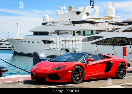 Front view of a red super sport car (Lamborghini) parked alongside luxury yachts moored in the marina of Puerto Banús. - Stock Photo