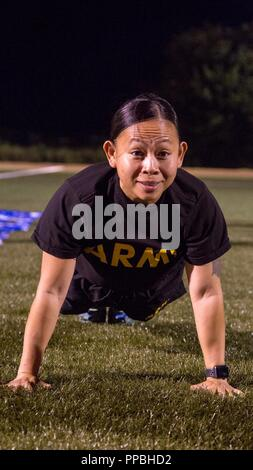 U.S. Army Drill Sgt. Lyra Lebron-Brown, a competitor in the Drill Sergeant Of The Year Competition, completes the push-up event of the Army Physical Fitness Test at Hellcat Field on Fort Sill, OK., Aug. 27, 2018. The Drill Sergeant Of The Year Competition is one of the most physically demanding and mentally tough challenges any Soldier can face in a U.S. Army competition. - Stock Photo
