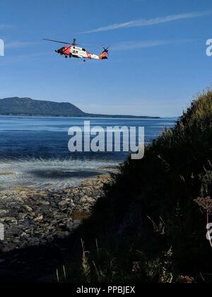 A Coast Guard Air Station Kodiak MH-60 Jayhawk helicopter aircrew conducts vertical surface training at Spruce Cape, in Kodiak, Alaska, Aug. 29, 2018. Kodiak-based search and rescue aircrew members are required to be vertical surface qualified in preparation for conducting cliff and mountain rescues across Alaska's rugged terrain. U. S. - Stock Photo