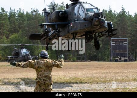 Sgt. Kole Lewsader, an AH-64 Apache armament, electrical and avionics systems repairer with 6th Squadron, 17th Cavalry Regiment, 4th Combat Aviation Brigade, 4th Infantry Division directs an AH-64 Apache Attack helicopter in the Forward Armor and Refueling Point while participating in the Saber Vortex training exercise in Grafenwoehr, Germany, August 29, 2018.  The exercise is part of 4th CAB's commitment to Atlantic Resolve, training alongside European allies to ensure the continued peace and stability in the region. - Stock Photo