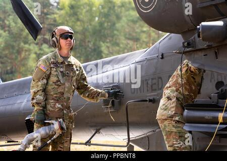 A Soldier with 6th Squadron, 17th Cavalry Regiment, 4th Combat Aviation Brigade, 4th Infantry Division prepares to fuel an AH-64 Apache attack helicopter in the Forward Armor and Refueling Point while participating in the Saber Vortex training exercise in Grafenwoehr, Germany, August 29, 2018.  The exercise is part of 4th CAB's commitment to Atlantic Resolve, training alongside European allies to ensure the continued peace and stability in the region. - Stock Photo