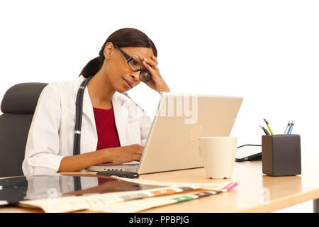 Stressed young female physician using laptop computer - Stock Photo