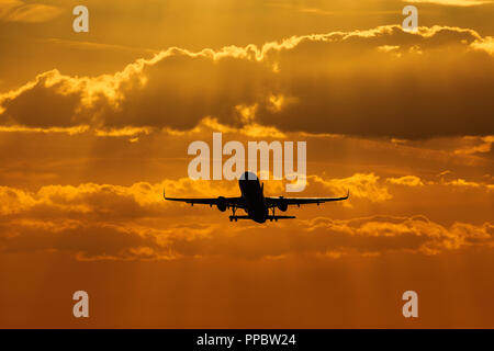 Luton Airport, London, UK. 24th Sep 2018. UK Weather: A silhouette of an Airbus A320 aircraft taking off at sunset Credit: Nick Whittle/Alamy Live News - Stock Photo