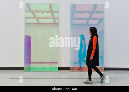 London, UK.  25 September 2018. A gallery staff member walks by 'Magic Mirrors (Pink #2 & Blue)', 2013-17, by Ann Veronica Janssens.  Preview of 'Space Shifters' at the Hayward Gallery, an exhibition which features artworks by 20 leading international artists that disrupt the visitor's sense of space and alter their perception of their surroundings.  The show runs 26 September to 6 January 2019.  Credit: Stephen Chung / Alamy Live News - Stock Photo