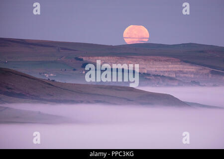 Hope Valley, Derbyshire, UK. 25th Sep 2018. The Full Moon sets over a mist-filled Hope Valley in The Peak District National Park in the early hours of 25th September 2018. Known as the Harvest Moon, the closest full moon to the Autumnal Equinox, it picks up an orange tinge from the sun rising in the opposite side of the sky. Credit: Graham Dunn/Alamy Live News - Stock Photo