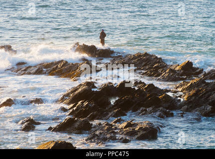 Newquay, Cornwall. 25th Sep 2018. UK Weather, Spring tide sea angler at Fistral Bay takes fishing to the white knuckle sport category as the high spring tide surrounds his extreme spot, defying unpredictable conditions. UK 25th, September, 2018 Credit: Robert Taylor/Alamy Live News - Stock Photo