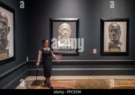 Royal Academy of Arts, London, UK. 25 September, 2018. The first major survey of Oceanic art to be held in the UK celebrating the art of Melanesia, Micronesia and Polynesia with around 200 works spanning 500 years. The exhibition marks the 250th anniversary of the RA, founded in 1768, the same year Captain James Cook set sail on his first expedition to the Pacific on Endeavour. Photo: Artist Fiona Pardington in front of her five large portaits from her acclaimed 'The Pressure of Sunlight Falling', a series of photographs of life casts made by medical scientist and phrenologist Pierre Dumoutier - Stock Photo