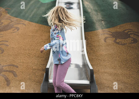 blonde girl facing away on slide in play park
