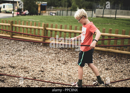 blond boy playing on a play park - Stock Photo