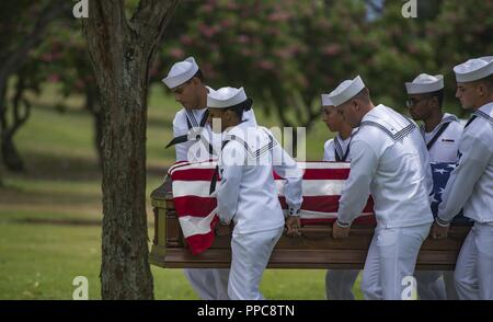 U.S. Navy honor guardsmen assigned to Navy Region Hawaii carry the casket of Machinist's Mate 1st Class Arthur Glenn at the National Memorial Cemetery of the Pacific, Honolulu, Hawaii, Aug. 21, 2018. On Dec. 7, 1941, Glenn was assigned to the USS Oklahoma which sustained fire from Japanese aircraft. The ship capsized after multiple torpedo hits, resulting in the deaths of more than 429 crew members at Ford Island, Pearl Harbor. Glenn is the 100th Oklahoma sailor identified through DNA analysis with the help of the Defense POW/MIA Accounting Agency (DPAA) and returned to his family for burial w - Stock Photo