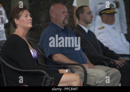 Family members of U.S. Machinist's Mate 1st Class Arthur Glenn attend his funeral at the National Memorial Cemetery of the Pacific, Honolulu, Hawaii, Aug. 21, 2018. On Dec. 7, 1941, Glenn was assigned to the USS Oklahoma which sustained fire from Japanese aircraft. The ship capsized after multiple torpedo hits, resulting in the deaths of more than 429 crew members at Ford Island, Pearl Harbor. Glenn is the 100th Oklahoma sailor identified through DNA analysis with the help of the Defense POW/MIA Accounting Agency (DPAA) and returned to his family for burial with full military honors. - Stock Photo
