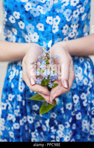 Plant with flowers in girl's hands. Ecology the cultivation of plants, the protection of the environment. Clean air, the preservation of the planet in - Stock Photo