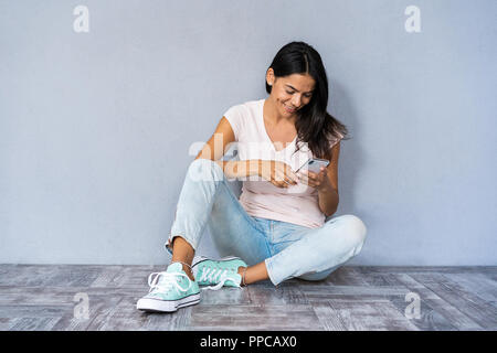 Happy brunette woman sitting on the floor and writing message on smartphone over gray background. - Stock Photo