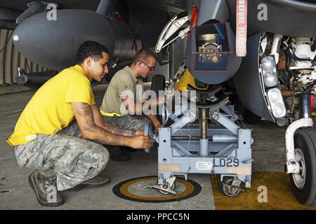"""Senior Airman Joseph Grullon (left) and Senior Airman Trevor Azeredo (right), 80th Aircraft Maintenance Unit weapons load crew members, prepare to remove a targeting pod from an 80th Fighter Squadron """"Juvats"""" F-16 Fighting Falcon at Kunsan Air Base, Republic of Korea, Aug. 24, 2018. The 80th AMU is working to prepare the fighter squadron to resume their flying operations. - Stock Photo"""