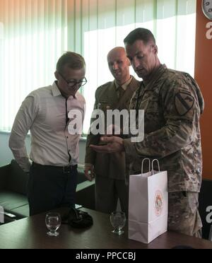 U.S. Army Lt. Col. Matthew Rogers, right, the commander of the 91st Engineer Battalion, 1st Armored Combat Brigade Team, 1st Calvary Division, gives a unit patch to Mateusz Dróżdż, the CEO of the Zagłębia Lubin soccer team, during his attendance of a Zagłębie Lubin soccer game in celebration of military appreciation night held in Lubin, Poland, Aug. 12, 2018. Polish army Maj. Jacob Wołynski, center, the athletic director with the 23rd Artillery Regiment, organized the event with the assistance of Dróżdż in honor of Polish Army Day. - Stock Photo