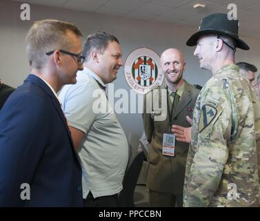 U.S. Army Lt. Col. Matthew Rogers, right, the commander of the 91st Engineer Battalion, 1st Armored Combat Brigade Team, 1st Calvary Division, meets with Marcin Chludziński, the president of KGHM Poland Copper and sponsor of the Zagłębie Lubin soccer team, during the military appreciation night held at the KGHM Zagłębie Lubin soccer stadium in Lubin, Poland, Aug. 12, 2018. Polish army Maj. Jacob Wołynski, center, the athletic director with the 23rd Artillery Regiment, organized the event with the assistance of Mateusz Dróżdż, left, the CEO of the Zagłębia Lubin soccer team, in honor of Polish  - Stock Photo