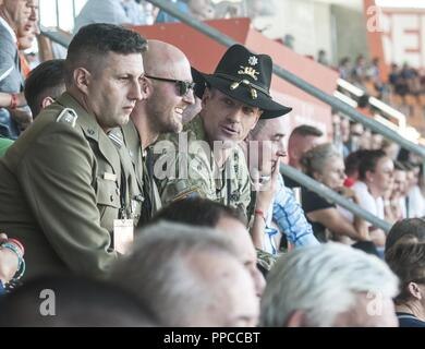 U.S. Army Lt. Col. Matthew Rogers, right, the commander of the 91st Engineer Battalion, 1st Armored Combat Brigade Team, 1st Calvary Division, enjoys the military appreciation night during his attendance of a Zagłębie Lubin soccer game with Maj. Jacob Wołynski, center, the athletic director with the 23rd Artillery Regiment, Polish Land Forces, held in Lubin, Poland, Aug. 12, 2018. Wołynski assisted in organizing the event for Polish and U.S. military personnel in honor of Polish Army Day. - Stock Photo