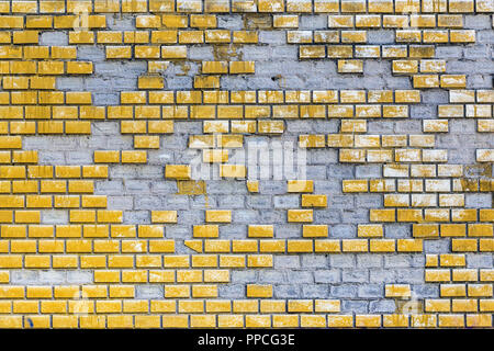 Old weathered yellow painted brick wall with elements missing. Aged block surface with parts fall off. Concrete grunge outdor urban background