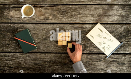 Research and brainstorming - top view of male hand placing wooden cubes in a square shape with charts, graphs and notes written on a piece of paper ly - Stock Photo