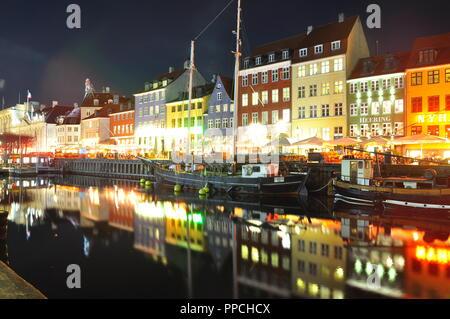 Nyhavn Harbour in Copenhagen, Denmark by night with water reflections