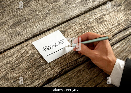 Peace concept written on a memo by a businessman seated at a rustic wooden table, close up of his hand and the handwritten note. - Stock Photo