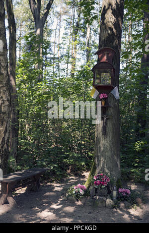 Small chapel suspended on a tree in a forest near Ostrzeszów, Poland. A sign of piety of the local population. - Stock Photo