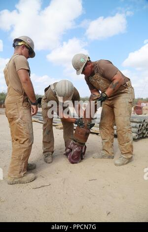 U.S. Navy Utilitiesman 2nd Class Anthony Calleja, (left), Construction Mechanic 2nd Class Hunter Patterson (center), and Equipment Operator 1st Class Dennis Hill (right), assigned to Naval Mobile Construction Battalion (NMCB) 133,  participate in water-well drilling exploration in Riohacha, Colombia, Sept. 3, 2018, as part of Southern Partnership Station 2018. Southern Partnership Station is a U.S. Southern Command-sponsored and U.S. Naval Forces Southern Command/U.S. 4th Fleet-conducted annual deployment focused on subject matter expert exchanges and building partner capacity in a variety of  - Stock Photo