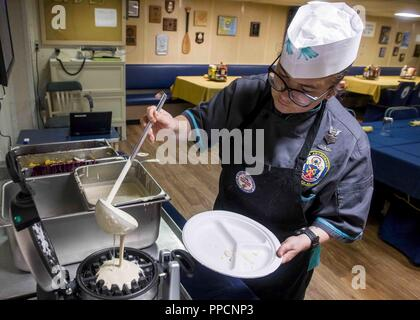 INDIAN OCEAN (Sept. 2, 2018) Culinary Specialist 1st Class Selia Arreguin, from Santa Barbara, Calif., prepares a meal aboard San Antonio-class amphibious transport dock USS Anchorage (LPD 23) during a regularly scheduled deployment of Essex Amphibious Ready Group (ARG) and 13th Marine Expeditionary Unit (MEU). The Essex ARG/13th MEU is a lethal, flexible, and persistent Navy-Marine Corps team deployed to the 5th Fleet area of operations in support of naval operations to ensure maritime stability and security in the Central Region, connecting the Mediterranean and the Pacific through the weste - Stock Photo