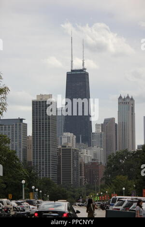 The John Hancock Center Building Tower and it's surrounding buildings as seen from the Lincoln Park Zoo as a partial Chicago skyline during the day. - Stock Photo