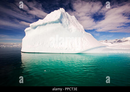 An iceberg in the Gerlache Strait separating the Palmer Archipelago from the Antarctic Peninsula off Anvers Island. The Antartic Peninsula is one of the fastest warming areas of the planet. - Stock Photo