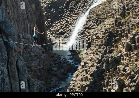 Young woman balancing on tightrope across Basaltic Prisms of Santa Maria Regla, Huasca de Ocampo, Hidalgo, Mexico - Stock Photo